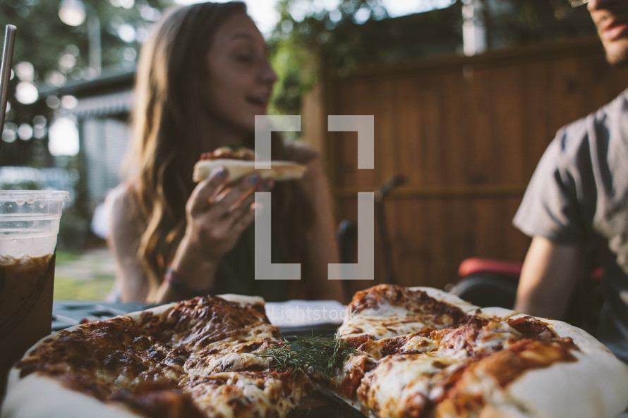 A woman eating pizza outdoors.