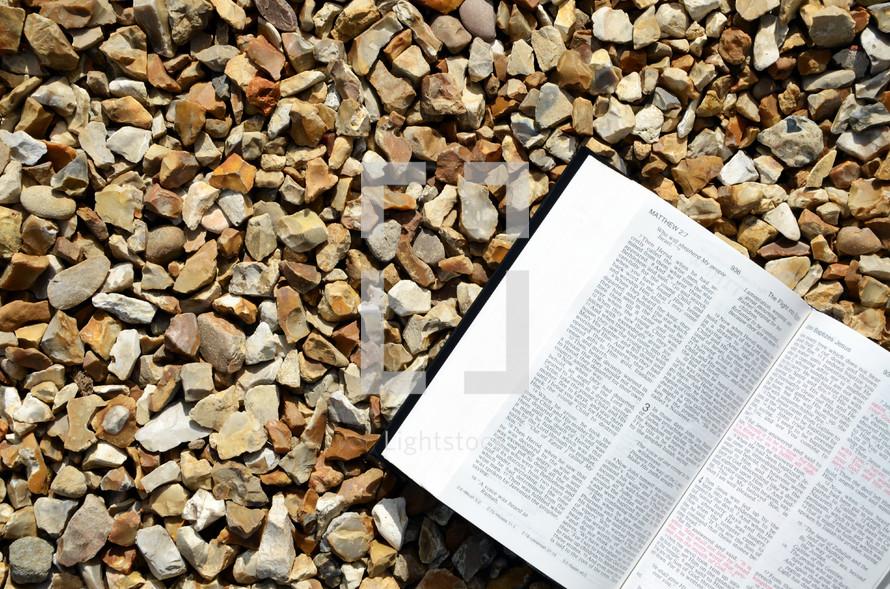 open Bible on gravel