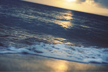 Ocean tide on the beach at sunset.