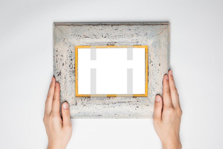hands holding up a frame