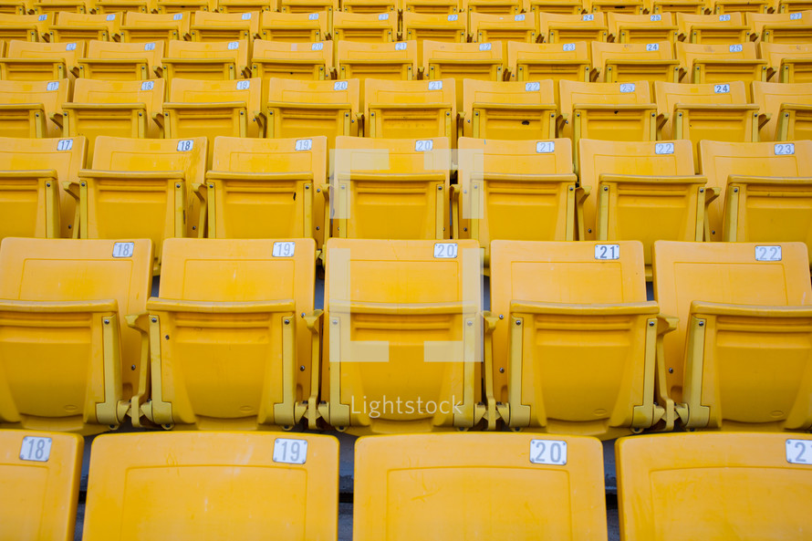 rows of yellow seats in a stadium