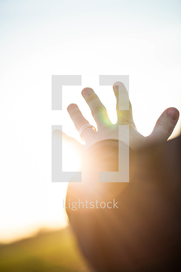 hand reaching out to God glowing in sunlight