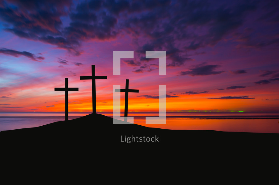 silhouette of three crosses on a hill at sunrise