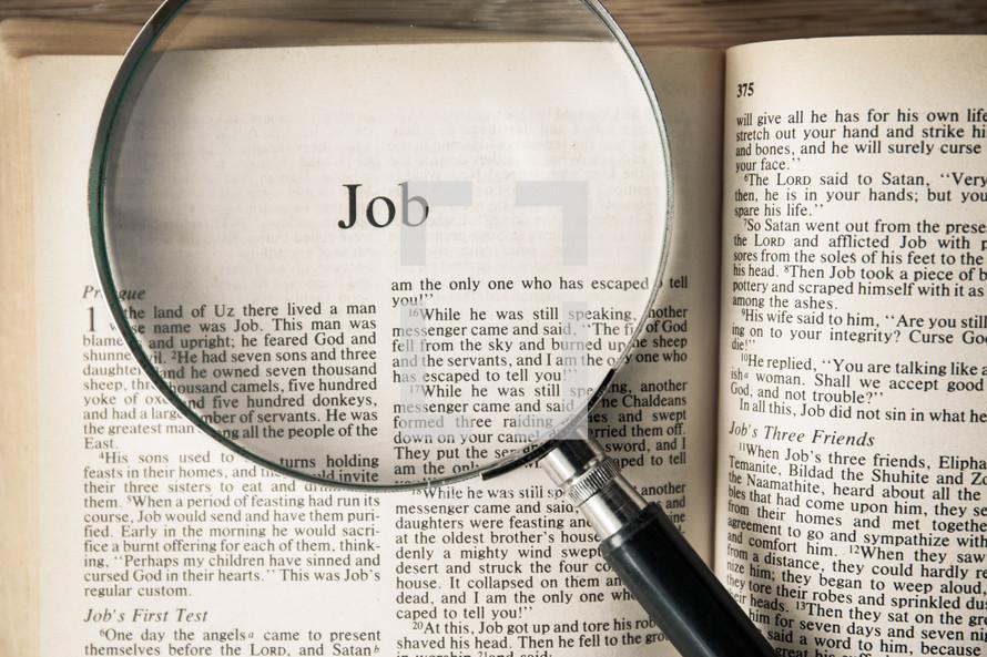magnifying glass over Bible - Job