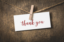 word thank you on white card stock hanging from a clothespin on a clothesline