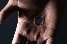Close up of hand with hole in it.