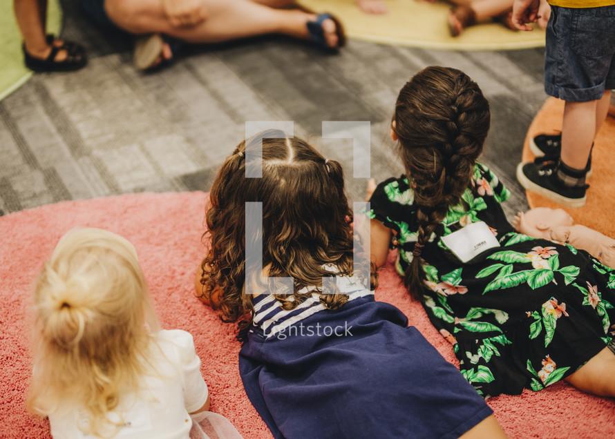 children sitting on the floor around a teach