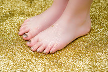 bare feet standing in glitter