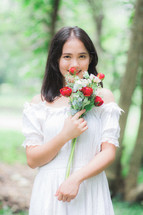 a woman holding red and white roses