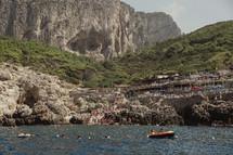 people swimming in the sea along an Italian shore