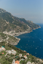 houses and churches on a mountainside along a coastline in Italy