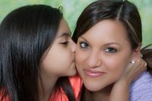 little girl kissing mother on the cheek