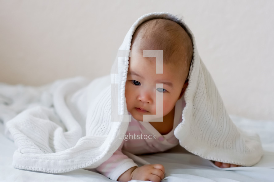 an infant under a blanket