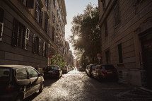 cars parked along narrow cobblestone streets in Rome