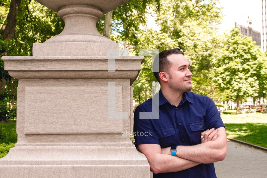 a man leaning on a stone statue