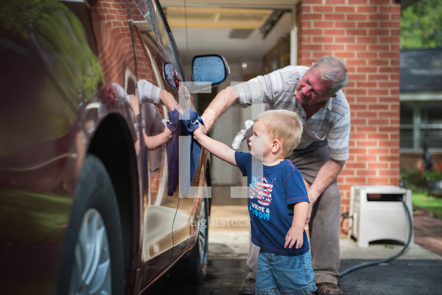 A small boy and his grandfather washing a car together.