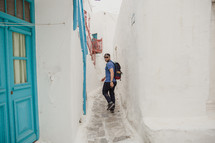 man walking in a narrow alley in Greece