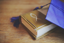 a mortar board and Bible