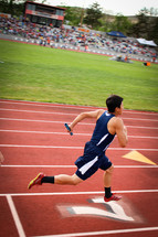 man running on a track in a relay race