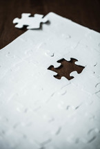White jigsaw puzzle with piece missing.