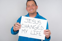 man holding a Jesus changed my life sign