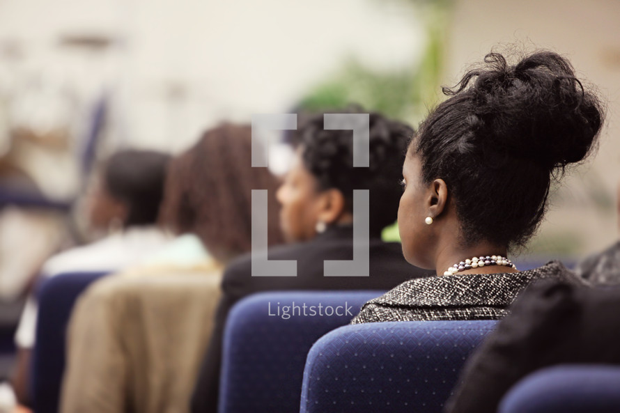 Profile of woman  seated in church service; attentively listening and watching preaching, women in background