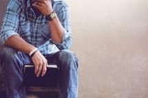 a man sitting holding a Bible