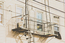 suspended balcony and fire escape ladder on the exterior of a building