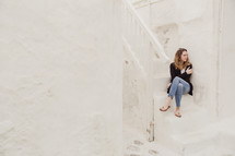 woman sitting on white steps in Greece