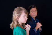 young girls with praying hands