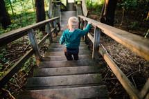 toddler boy walking down steps outdoors
