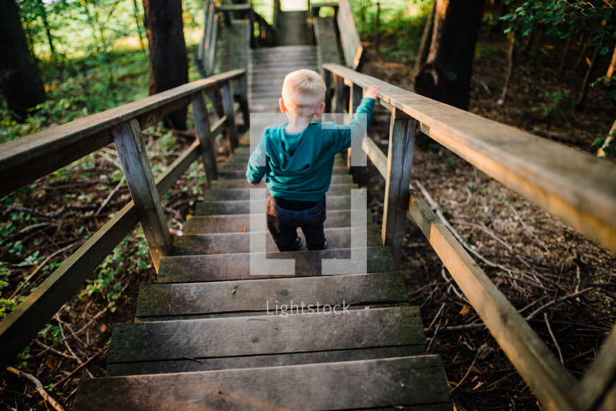 toddler boy walking down steps outdoors