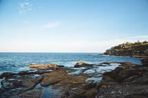 A rocky shore lining the ocean.