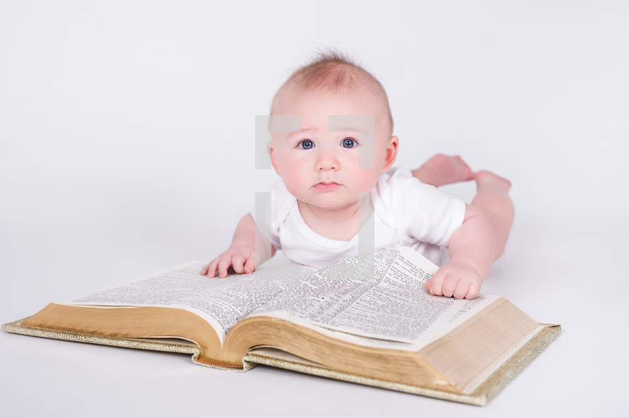 Baby dressed in white, laying on the floor with his propped on a giant bible