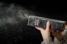 blowing off dust from a Bible
