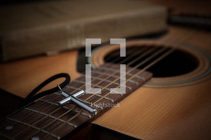 cross necklace, acoustic guitar, and Bible
