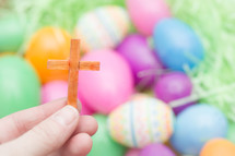 hand holding a small wooden cross and plastic Easter eggs