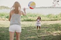 A woman tosses a beach ball to a little girl.