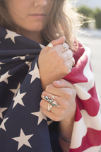 A young woman wrapped in an American flag