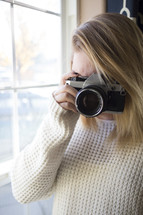 a woman in a sweater taking a picture with a camera