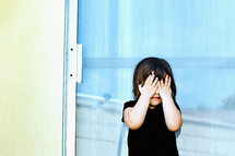 a child covering his face