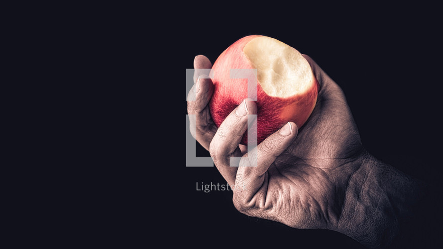 Hand holding an apple with a bite mark