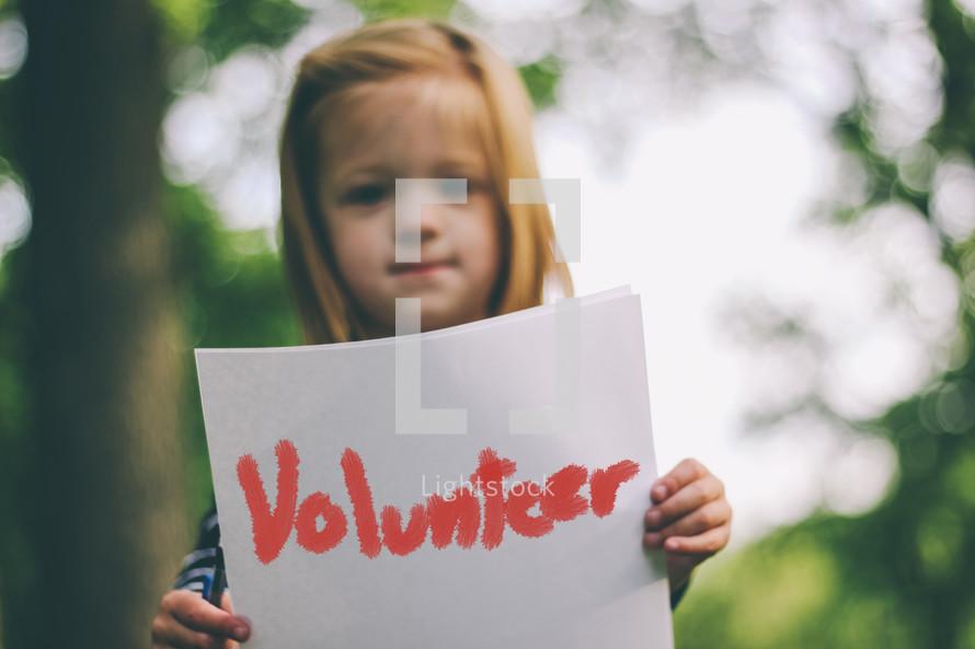 girl holding volunteer sign