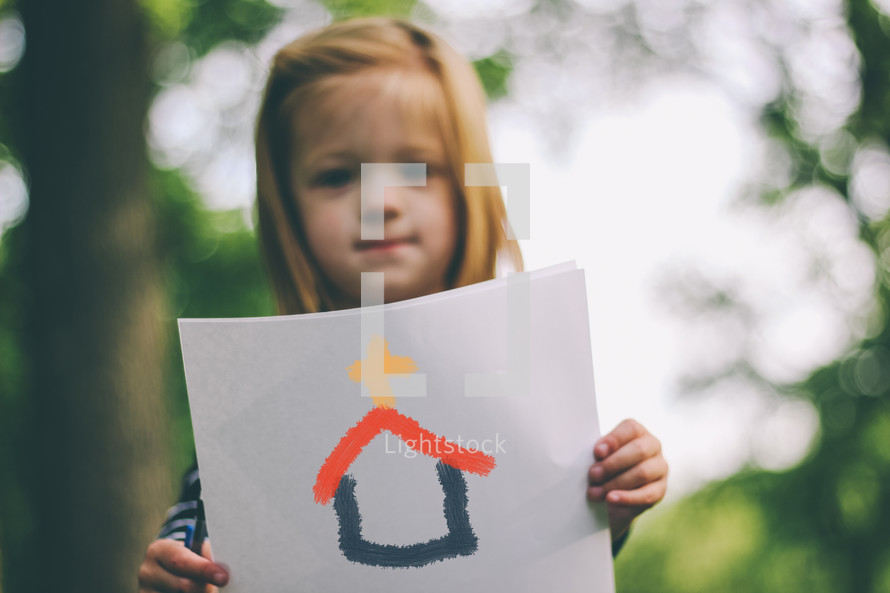 A child holding a drawing of a church.