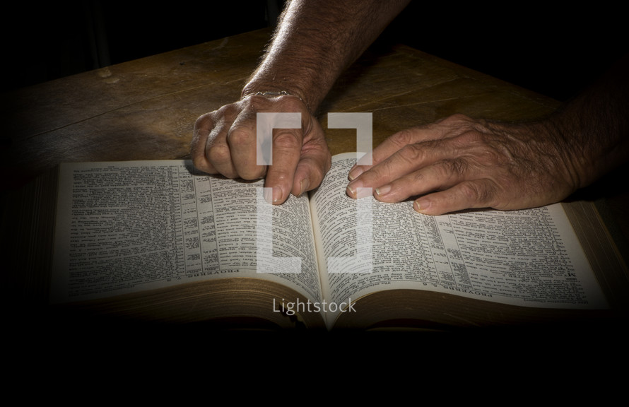 man pointing to a verse on the page of a Bible