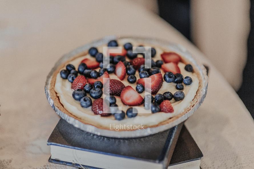fruit tart on a stack of books