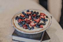 fruit tart on a stack of books