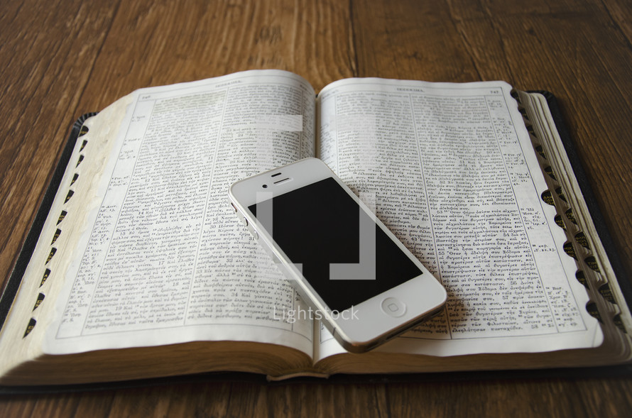cellphone on the pages of an open Bible on a wood floor