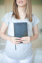 Smiling woman holding closed Bible.