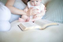 Mother holding daughter up on the bed as she looks at an open Bible.